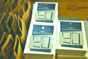 """DĀVANU GALDS. Grāmatas """"Cēsu valsts ģimnāzijai 90"""" un suvenīri."""