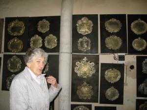 DZIMTAS VĒSTURE. Straupes draudzes locekle un baznīcas gide Ausma Antonišķe pie epitāfiju sienas, kas izveidota līdzās ērģelēm. Foto: SARMĪTE FELDMANE