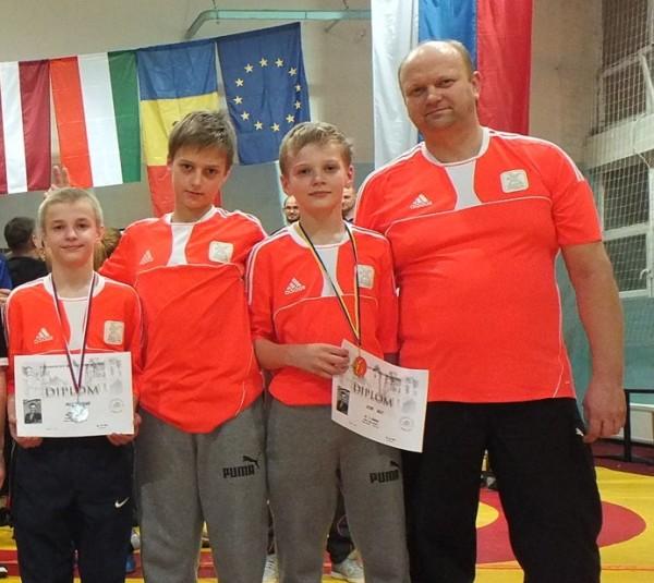"""VEIKSMĪGI. Starptautiskajā turnīrā Slovākijā veiksmīgi startēja kluba """"Ferrum"""" jaunie cīkstoņi Ingars Polis (no kreisās), Rainers Lūkins un Ralfs Lūkins. Kopā ar viņiem komandas pārstāvis Dainis Lūkins. Foto: NO ALBUMA"""