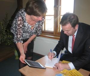 """Viljams Duglass savā grāmatā latviešu valodā pirmajai ierakstu veic izdevniecības """"Zvaigzne ABC"""" vadītājai Vijai Kilblokai."""